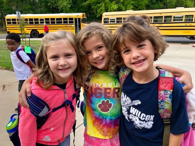 three students wearing spirit wear standing outside school