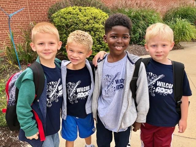 four students wearing spirit wear