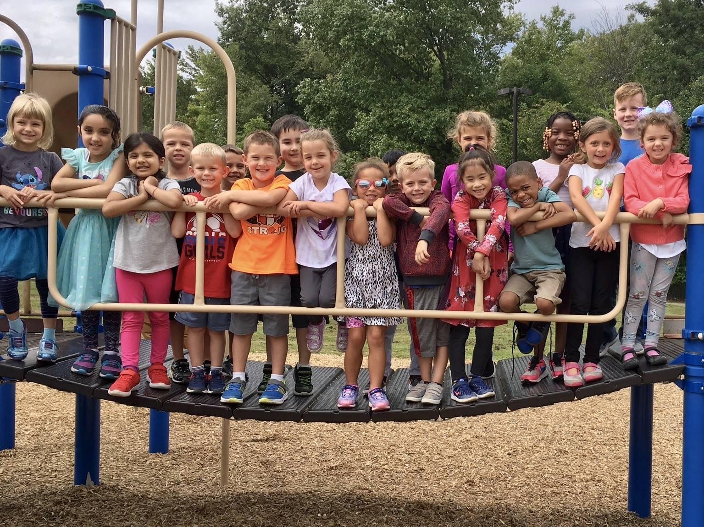 students standing on playground bridge