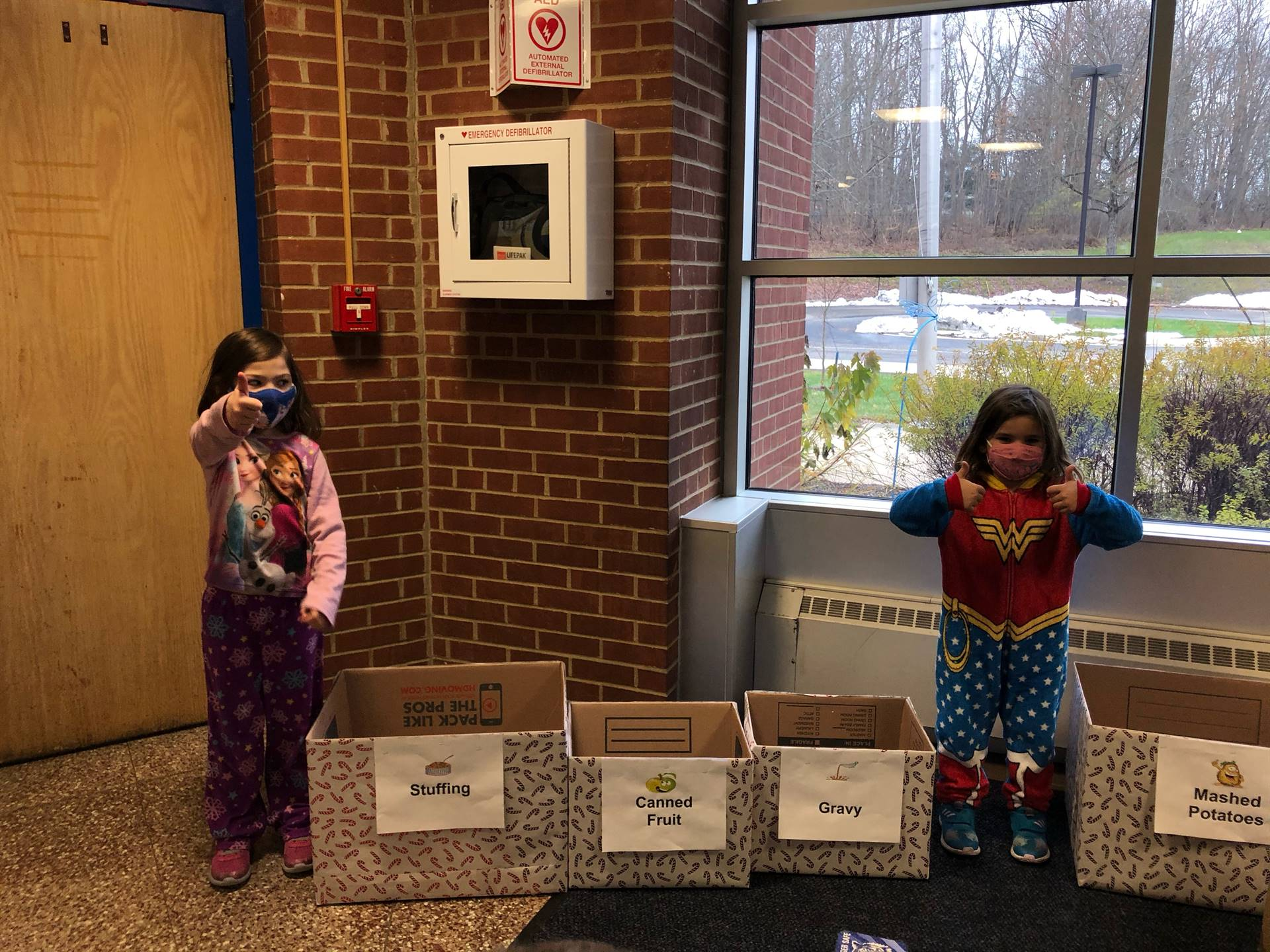 students standing by donation boxes
