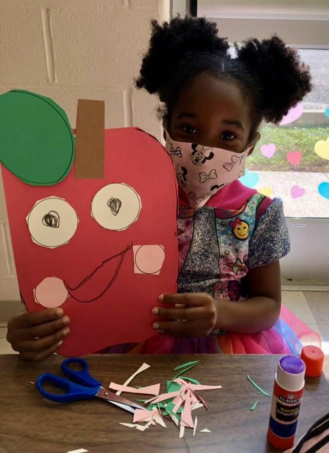 student holding apple craft