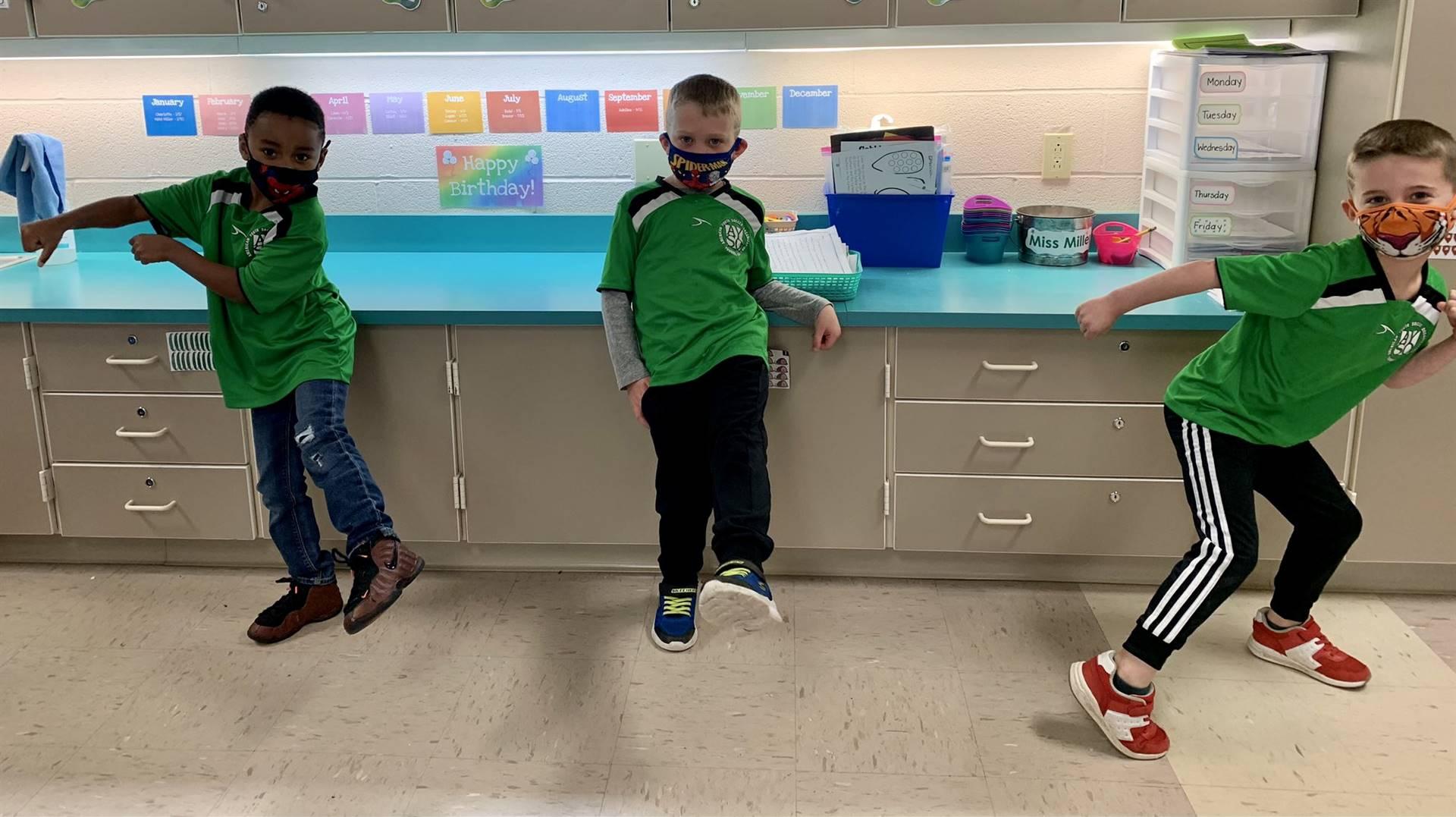 three students wearing matching green shirts