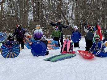 Students standing with sleds on a hill