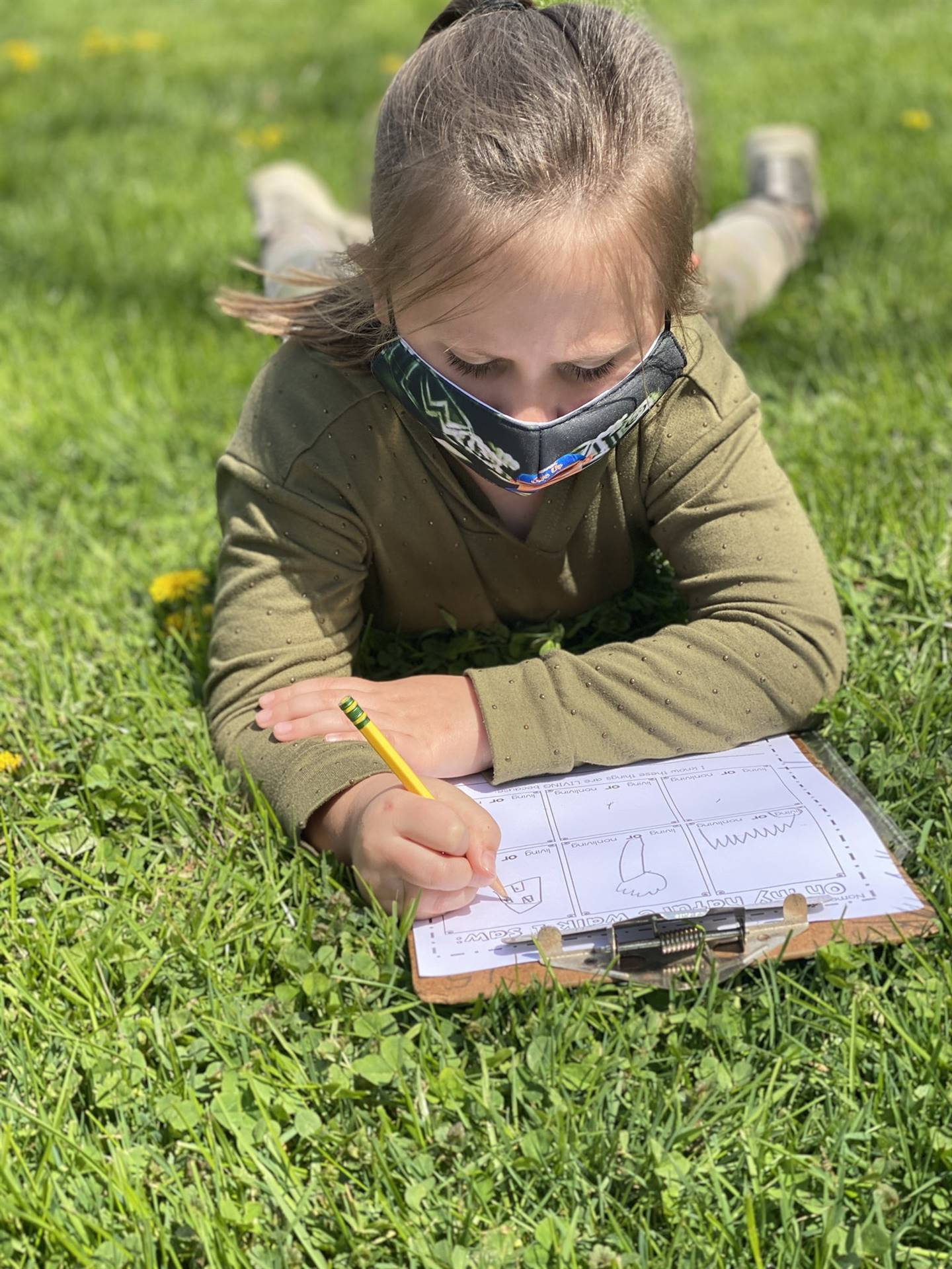 student laying in grass writing on clipboard