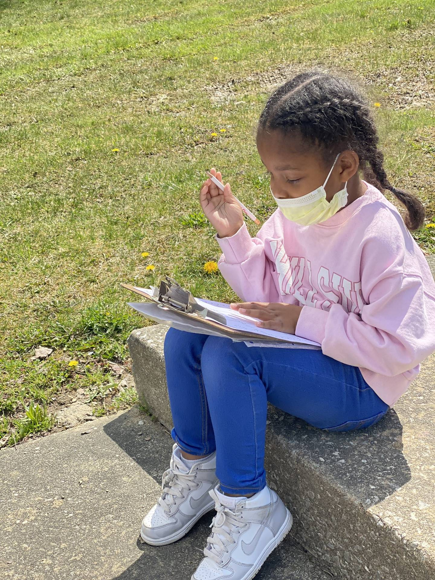 student sitting on steps outside writing on clipboard