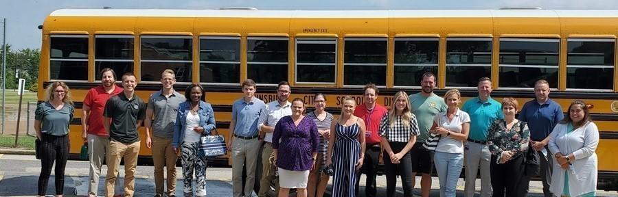 new staff standing in front of school bus