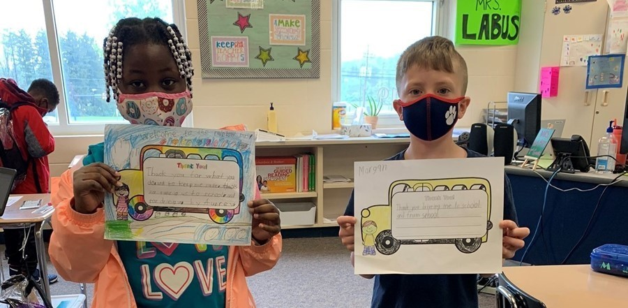 students holding thank you notes to bus drivers
